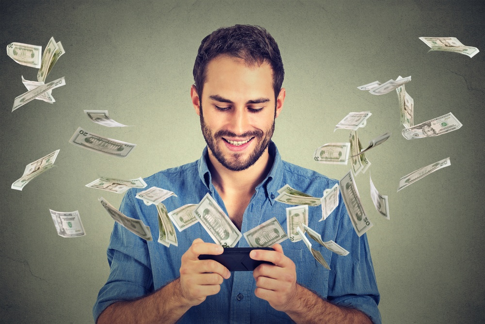 Technology online banking money transfer, e-commerce concept. Happy young man using smartphone with dollar bills flying away from screen isolated on gray wall office background..jpeg